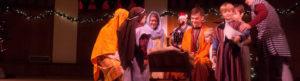 Children dressed as shepherds adoring Jesus