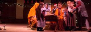 Kids dressed as shephered adoring baby Jesus