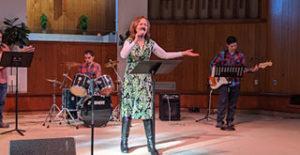 Female worshiper singing with hand raised